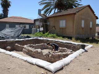 עובד רשות העתיקות לצד בסיס המבנה מתקופת הברונזה, ובתי המושב. צילום: יוֹלי שוורץ, באדיבות רשות העתיקות