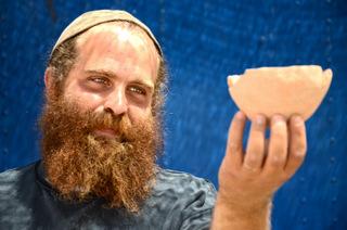 הארכיאולוג בנימין סטורצ'ן עם קערה מתקופת הברונזה. צילום: יוֹלי שוורץ, באדיבות רשות העתיקות